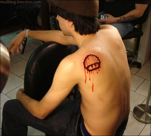 The guy seems to relax as the blood oozes out of the newly inked Mario